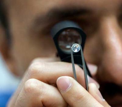 Étude d'un diamant blanc à la loupe par un diamantaire